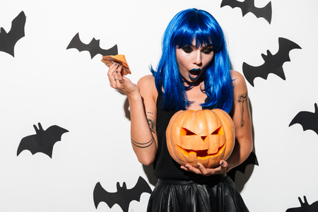 Picture of emotional gorgeous young woman in witch halloween costume on party over white background with pumpkin. Looking aside.