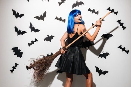 Photo of emotional screaming young woman in witch halloween costume on party over white background with broom. Looking camera. 스톡 콘텐츠