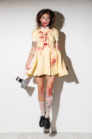 Full length image of frightening zombie woman in dress like flying with an axe in hand and looking at the camera over white background