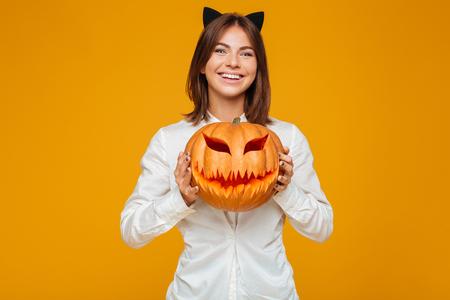 Bild der netten jungen Frau kleidete im verrückten Katzenhalloween-Kostüm über gelbem Hintergrund mit Kürbis an. Standard-Bild - 87992519