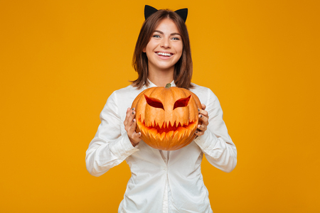 Image of cheerful young woman dressed in crazy cat halloween costume over yellow background with pumpkin. Stock Photo