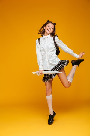 Full length portrait of a cheerful young schoolgirl in uniform holding umbrella and posing while jumping and looking at camera isolated over orange background Stock Photo