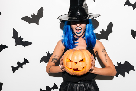 Image of emotional amazing young woman in witch halloween costume wearing hat on party over white background with pumpkin.