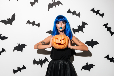 Image of emotional amazing young woman in witch halloween costume on party over white background with pumpkin. Looking camera.