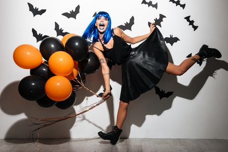 Image of emotional young woman in witch halloween costume wearing hat on party over white background with balloons.
