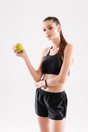 sportwoman: Portrait of a young attractive sportwoman holding green apple and looking at camera isolated over white background