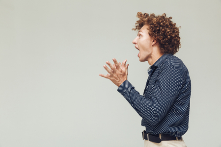 Image of young shocked retro man dressed in shirt standing and posing isolated. Looking aside screaming.