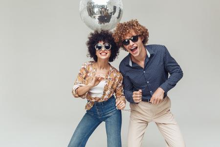 Bild der jungen emotionalen lächelnden Retro- liebevollen Paare, die lokalisiert stehen und aufwerfen. Schauen der Kamera, die nahe Discokugel tanzt. Standard-Bild