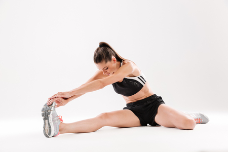 sportwoman: Full length portrait of a healthy motivated sportwoman stretching muscles while sitting on the floor isolated over white background
