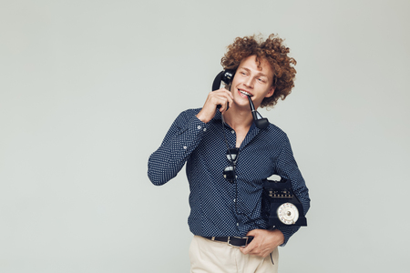 Picture of young handsome retro man dressed in shirt standing and posing isolated. Looking aside with telephone in hands. Banco de Imagens