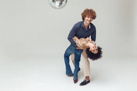 Picture of young emotional cheerful retro loving couple standing and posing isolated. Looking camera dancing near disco ball.