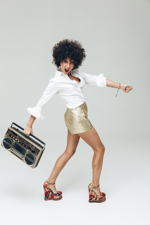 Photo of young emotional retro woman dressed in shirt standing and posing isolated. Looking camera holding boombox.