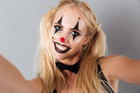 Close up portrait of a smiling blonde woman in bright halloween clown make-up taking a selfie isolated over gray background
