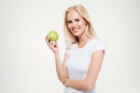 Portrait of a happy fit woman holding green apple and looking at camera isolated over white background Stock Photo