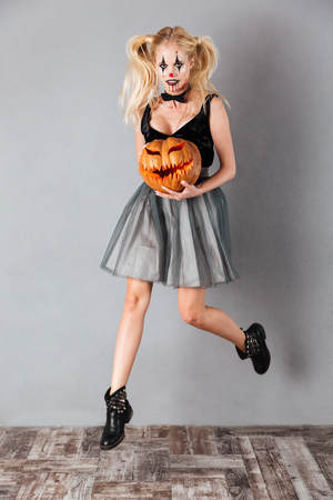 Full length portrait of a scary crazy blonde woman in halloween clown make-up and blood streaks holding curved pumpkin and jumping isolated over gray background Stock Photo