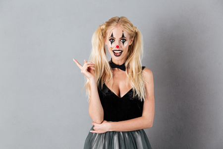 Happy blonde woman in halloween make up having idea and looking at the camera over gray background Stock Photo