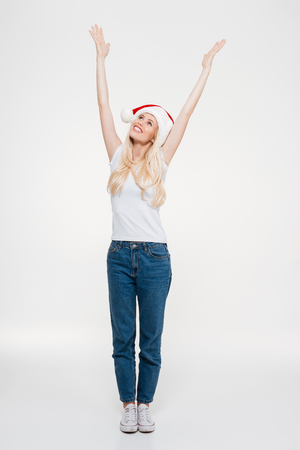 Full length portrait of cheerful pretty blonde woman in Santas hat with hands on the top, looks up, isolated on white background