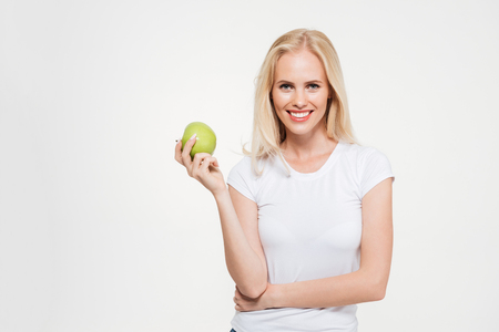 Portrait of a young healthy woman holding green apple and looking at camera isolated over white background