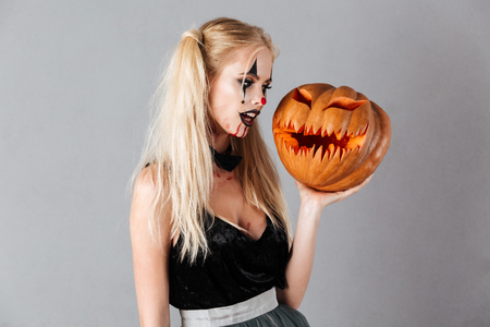 Pretty blonde woman in halloween make up holding carved pumpkin over gray background