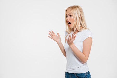Portrait of a shocked pretty woman gesturing with hands while looking away at copy space isolated over white background