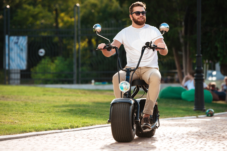 road bike: Full length image of happy bearded man in sunglasses rides on modern motorbike outdoors and looking away Stock Photo