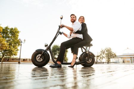 road bike: Full length side view image of joyful business couple rides on modern motorbike in park and looking away