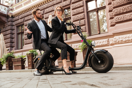 full length mirror: Full length side view image of Displeased bearded business man sitting on modern motorbike outdoors with young elegant woman which looking at mirror Stock Photo