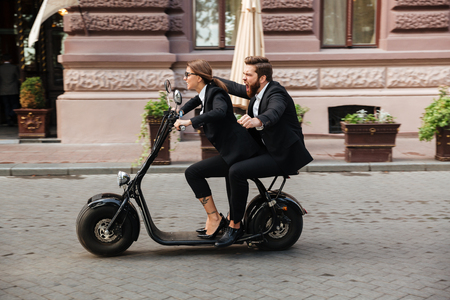 Cheerful excited couple wearing smart clothes riding motor bicycle on a city street