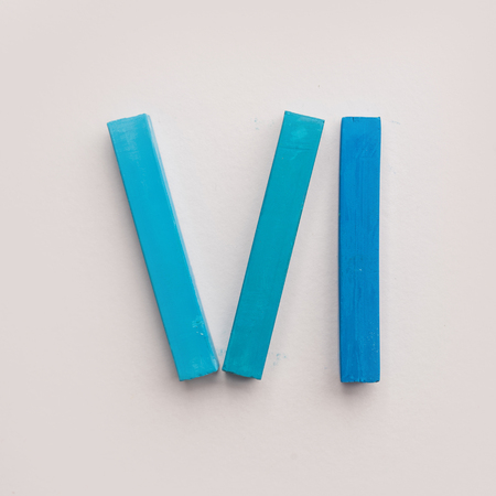 Six pieces of blue pastel crayon chalks isolated over white background Фото со стока