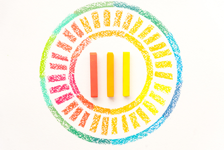 Top view of circle drawn with colorful pastel chalks on white background Stock Photo