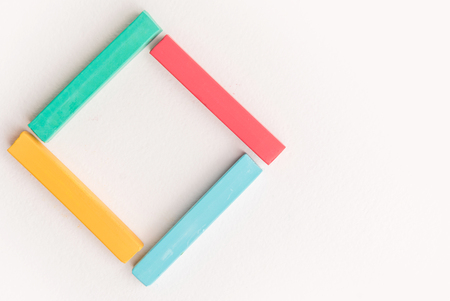 Close up of colorful pastel crayons, laid out in square, over white background Stock Photo