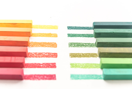 Cropped photo of colorful pastel chalks and their pigments on white background Фото со стока
