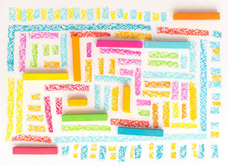 Top view of a bright geometric pattern made of colorful kids pastel chalks over white background Фото со стока