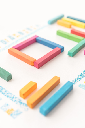 Cropped photo of geometric pattern made of colorful pastel chalks over white background
