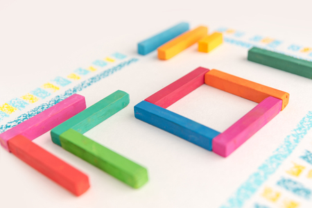 Cropped photo of a cute geometric pattern made of colorful pastel chalks over white background Stock Photo - 88181395