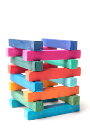 Close up of hight colorful chalks tower, isolated over white background Stock Photo