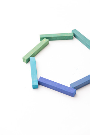 Cropped photo of colorful chalks in geometric composition, isolated on white background