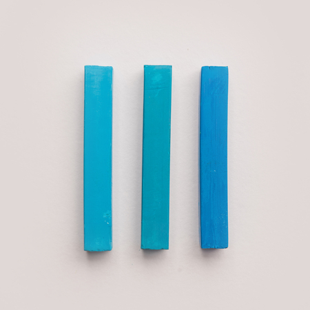 Three pieces of blue pastel crayon chalks isolated over white background