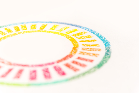 Cropped photo of circle drawn with colored pastel chalks, over white background