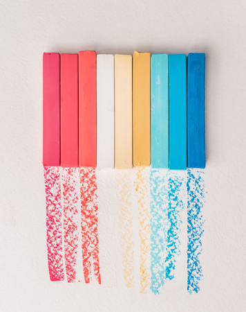 Bunch of square colorful pastel chalks and their pigments on white background