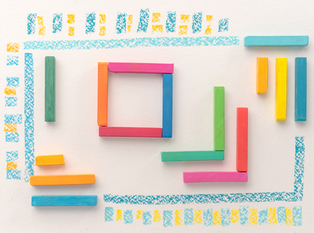 Top view of a cute geometric pattern made of colorful kids pastel chalks over white background
