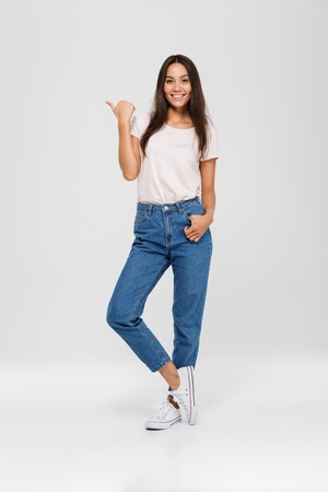 Full length portrait of a casual pretty asian woman standing and pointing finger away at copy space isolated over white background Banco de Imagens