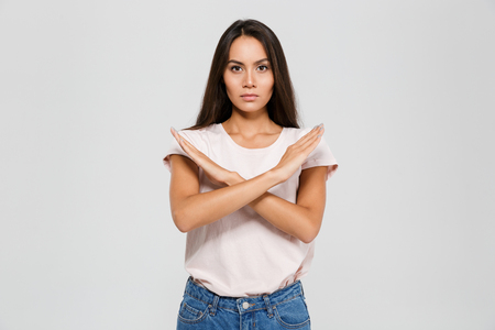 Portrait of a serious concentrated asian woman standing with crossed hands showing stop gesture isolated over white background Фото со стока