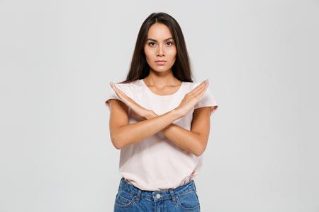 Portret van een ernstige geconcentreerde Aziatische vrouw die zich met gekruiste handen bevindt die eindegebaar tonen die over witte achtergrond wordt geïsoleerd