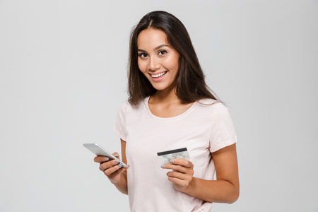 Portrait of a smiling happy asian woman holding credit card and mobile phone while looking at camera isolated over white background Standard-Bild