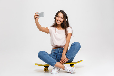 Portrait of young cheerful girl in white headphone makes selfie on smartphone, sitting on yellow skateboard, isolated over white background