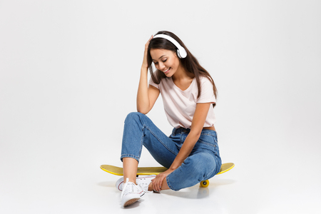 Cheerful young brunette woman in white headphones touching her head while sitting on yellow skateboard, isolated over white background Stock Photo