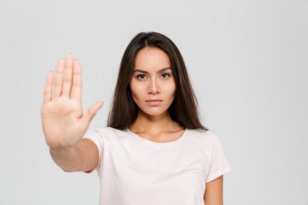 Ritratto di una donna asiatica giovane seria che sta con il gesto steso di arresto di rappresentazione della mano isolato sopra fondo bianco