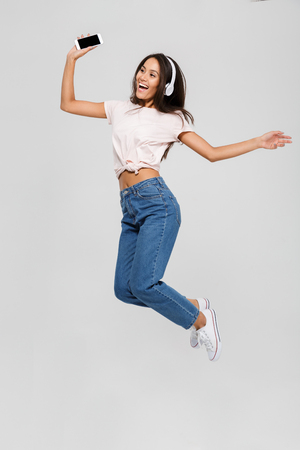Full length portrait of a joyful satisfied asian woman in headphones listening to music and jumping isolated over white background
