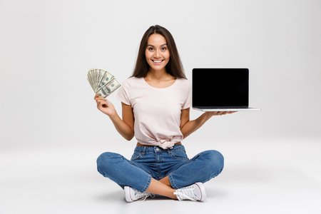Portrait of a smiling satisfied asian girl holding money banknotes while sitting with blank screen laptop computer and looking at camera isolated over white background